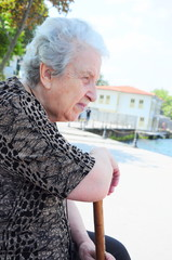 a senior woman resting at park by sea