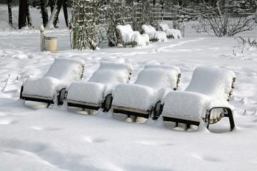 Verschneite Stühle in einem Stadtpark