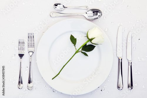 Table place setting with white rose on the plate