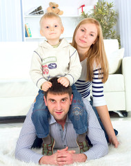 Happy family playing at home, lying heaped on floor