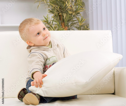 Portrait of little boy sitting at couch, smiling.