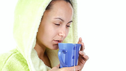Suffering from a cold woman drinking a tea, over white