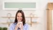 lächelnde frau trinkt kaffee in der küche