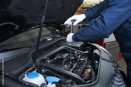 mechanic repairs a car in a garage