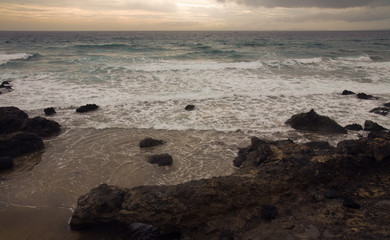 Shore of Lanzarote, wintry unsettled sea, outline of Fuerteventu
