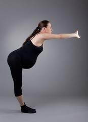 Pregnant woman doing gymnastic exercises on grey background.