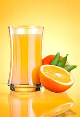Glass of Fresh Orange juice on yellow background