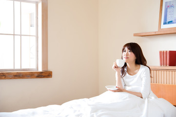 attractive asian woman drinking on the bed