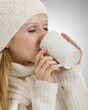 beautiful girl in winter clothes drinking warming drink