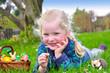 Mädchen liegt auf einer Wiese mit Osterkörbchen