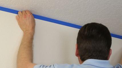 Man Applying Blue Painter's Tape on Wall Below Ceiling