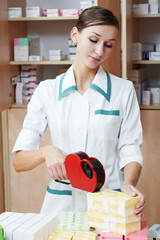 Pharmacy chemist woman labeling drugs
