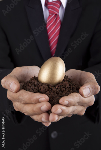Investment concept businessman with golden egg and soil