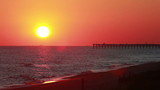 Beach with fishing pier sunset
