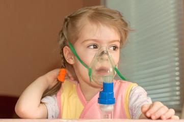 A little girl three years doing inhalation
