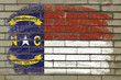 grunge flag of US state of north carolina on brick wall painted