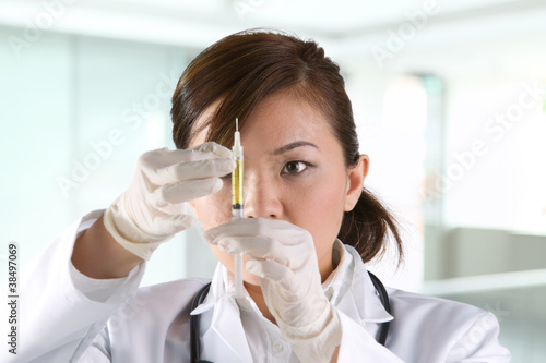 Portrait of a Female doctor holding a syringe.