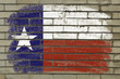 grunge flag of US state of texas on brick wall painted with chal