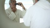 Senior man shaving with electric razor; Full HD Photo JPEG