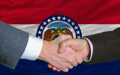 in front of american state flag of missouri two businessmen hand