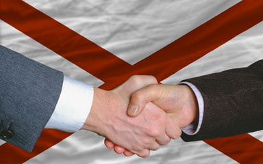 in front of american state flag of alabama two businessmen hands