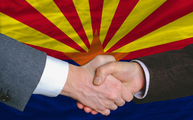 in front of american state flag of arizona two businessmen hands