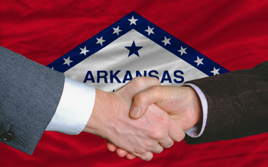 in front of american state flag of arkansas two businessmen hand
