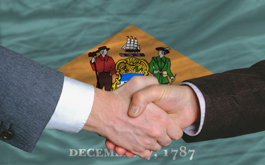 in front of american state flag of delaware two businessmen hand