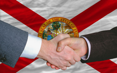 in front of american state flag of florida two businessmen hands