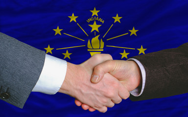 in front of american state flag of indiana two businessmen hands