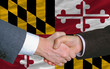 in front of american state flag of maryland two businessmen hand