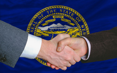 in front of american state flag of nebraska two businessmen hand