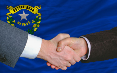 in front of american state flag of nevada two businessmen handsh