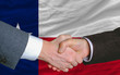 in front of american state flag of texas two businessmen handsha
