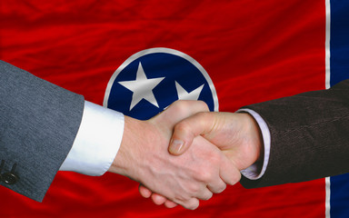 in front of american state flag of tennessee two businessmen han