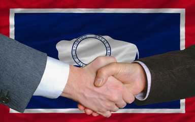 in front of american state flag of wyoming two businessmen hands