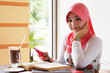 Young muslim stylish women smile while writing text messaging