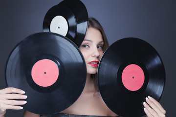 beautiful girl with vinil disc on black background