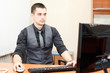 Portrait of smart young businessman working on computer