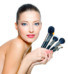 Beautiful woman with make-up brushes