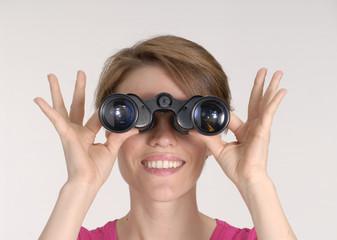 Mujer observando a través de unos binoculares.