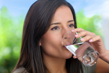 Portrait of smiling woman holding glass of water