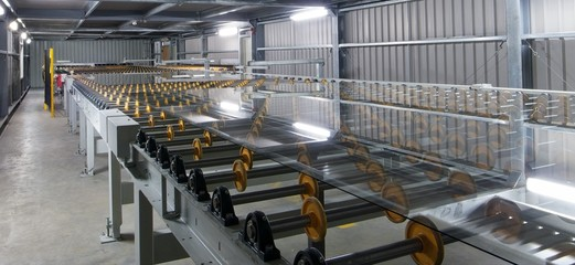 Large sheets of glass on rollers.