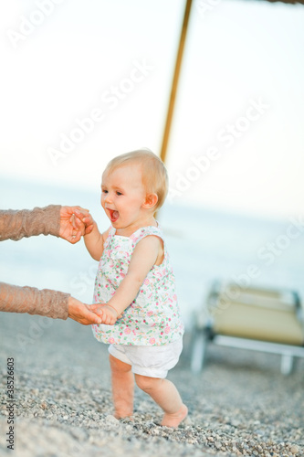 Happy baby on beach trying to start walking