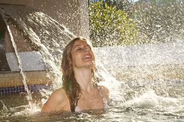 Woman under a spa waterfall
