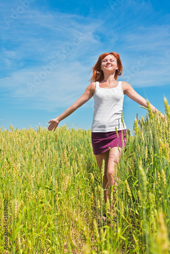 Beautiful young woman running through a wheat field