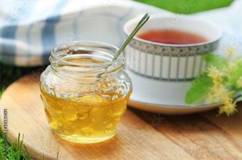 Linden honey in a jar with linden flowers