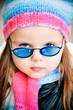 Portrait of beautiful little blond girl in glasses outside
