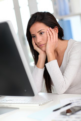 Woman in front of desktop computer having a headache