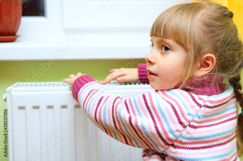 Girl warm one's hands near radiator